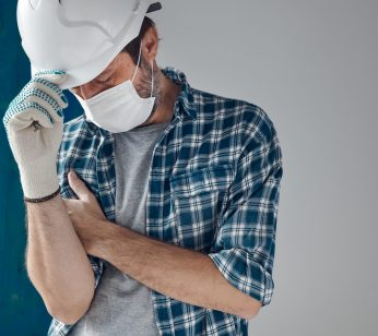 Worried construction engineer with protective face mask